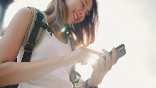 Cheerful asian backpacker blogger woman using smartphone for direction and looking on location map Free Photo