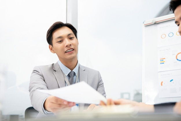 Cheerful asian businessman suggesting business plan document to client Premium Photo