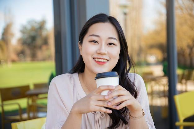 Cheerful asian coffee lover enjoying morning Free Photo
