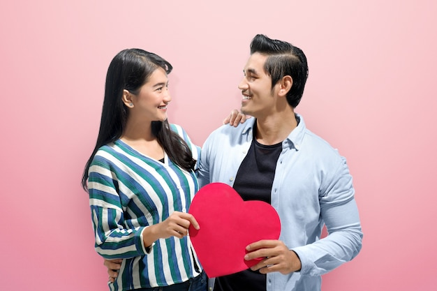 Cheerful asian couple embrace and holding red paper hearts Premium Photo