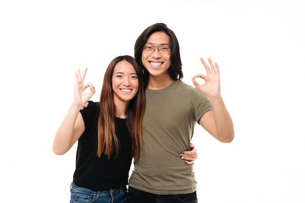 Веселые азиатские пары, показывая ок жест, обнимая друг друга, глядя на камеру Бесплатные Фотографии