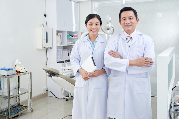 Cheerful asian dentists posing in treatment room in clinic in front of equipment Free Photo