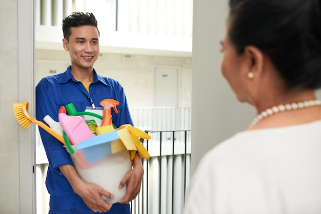 Cheerful asian janitor with tools standing at door and talking with wealthy female homeowner Free Photo