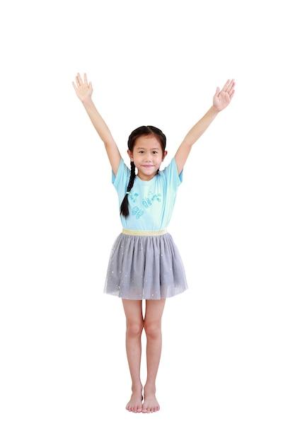 Веселая азиатская маленькая девочка с косичками стоит и поднимает руки вверх изолированной на белой стене Premium Фотографии
