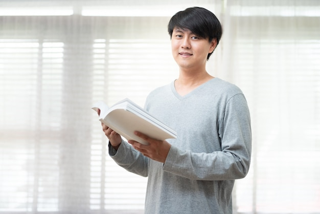 Cheerful asian man dress in casual standing relax in cafe hand hold book look at camera for data research and self improvement.education and scholarship opportunity.world book day concept. Premium Photo
