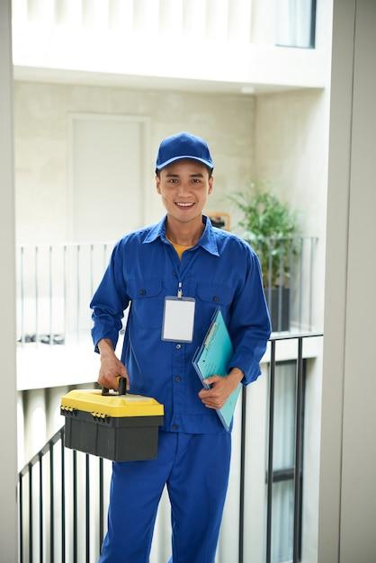 ツールボックスでドアに立っているオーバーオールで陽気なアジアの配管工 無料写真