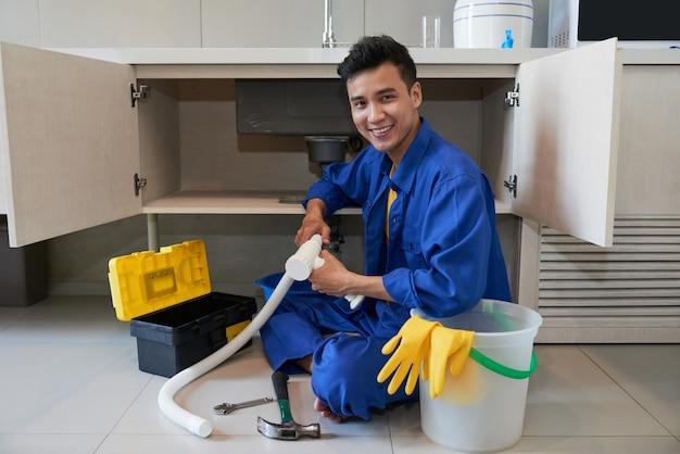 床に座って、台所の流しを修理する陽気なアジアの配管工 無料写真