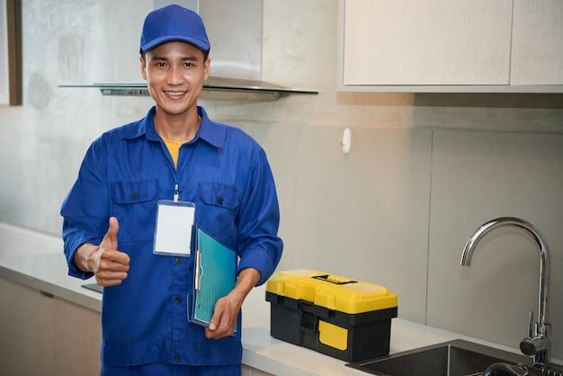 台所の流しの近くに立って、親指を現して陽気なアジアの配管工 無料写真