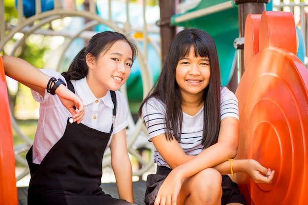 Cheerful asian teenager laughing in children playground Premium Photo