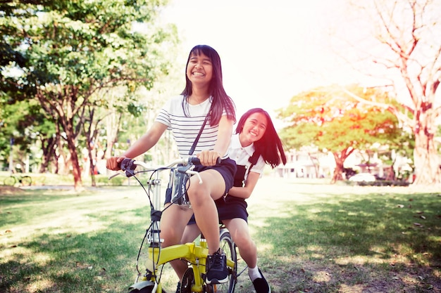 Cheerful asian teenager riding bicycle in pulbic park Premium Photo