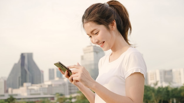 Жизнерадостная азиатская туристская женщина блоггера используя smartphone для направления и смотря на карте местоположения пока путешествующ на улице в городском городе. Бесплатные Фотографии