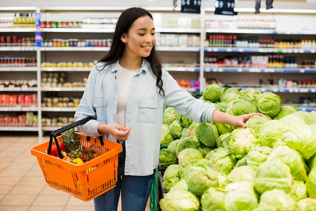 Cheerful asian woman choosing cabbage in market Free Photo