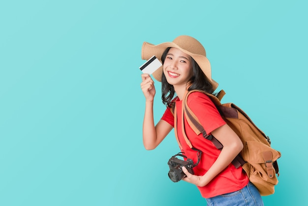 Cheerful asian woman holding credit card ready to travel Premium Photo