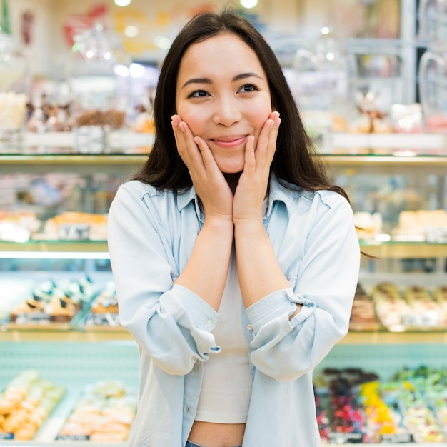 Cheerful asian woman standing with hands on cheeks in bakery store Free Photo