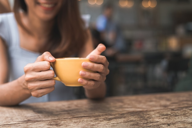 Cheerful asian young woman drinking warm coffee or tea enjoying it while sitting in cafe Free Photo