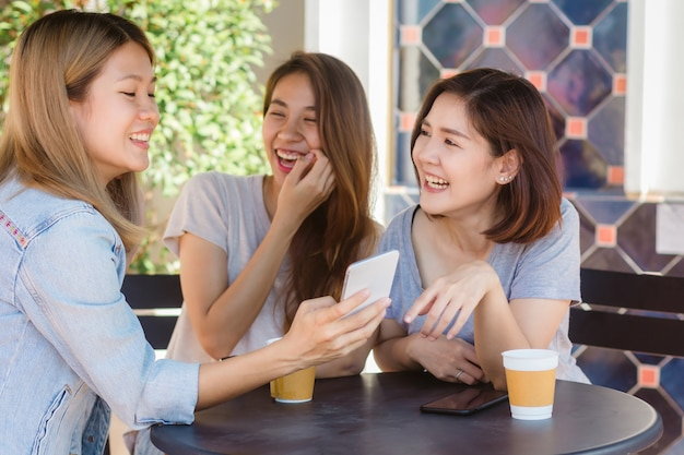 Young women sitting in cafe drinking coffee with friends and talking together - Freepik