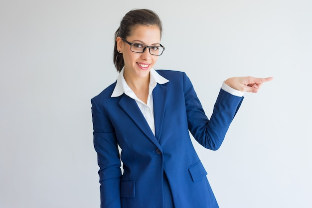 Cheerful attractive business lady pointing aside and looking at camera. Free Photo