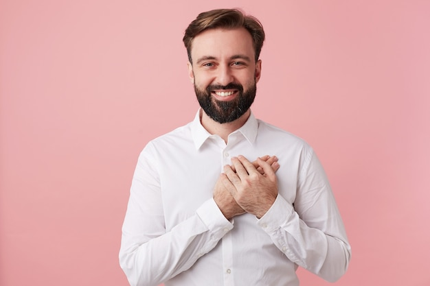 Cheerful attractive unshaved dark haired guy with short haircut keeping palm on his heart Free Photo