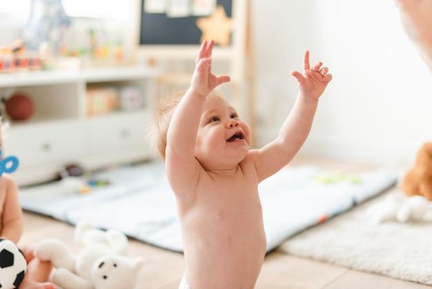 Cheerful baby reaching out to his mum Premium Photo