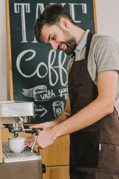 Cheerful barista pouring coffee Free Photo