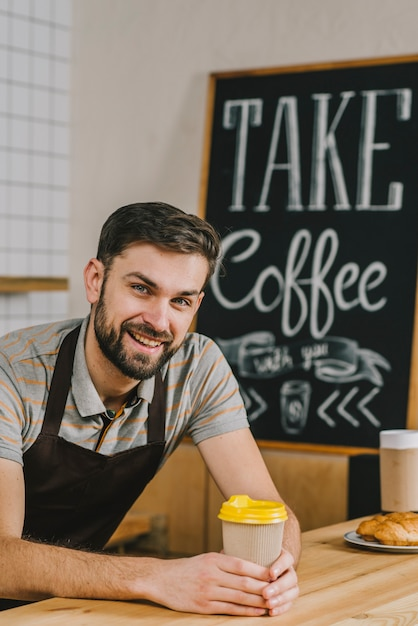 Cheerful barista with hot drink Free Photo