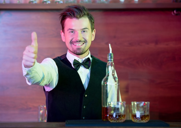 Cheerful barman is standing in a suit and showing thumbs up Premium Photo