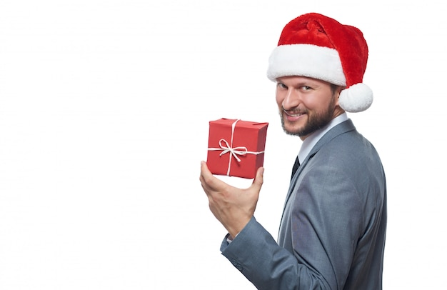 Cheerful bearded businessman in christmas hat smiling over shoulder keeping small christmas gift. Premium Photo