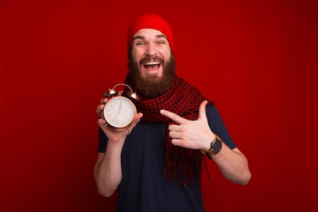 ヴィンテージ時計を指して、カメラでこれを示す赤いスペースの陽気なひげを生やした男 Premium写真