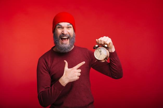 目覚まし時計を指す赤いスペースの上に立っている陽気なひげを生やした男 Premium写真