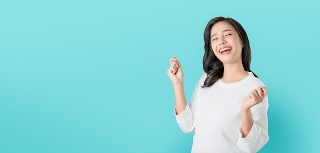 Cheerful beautiful asian woman in casual white t-shirt and happy face smile on blue background Premium Photo