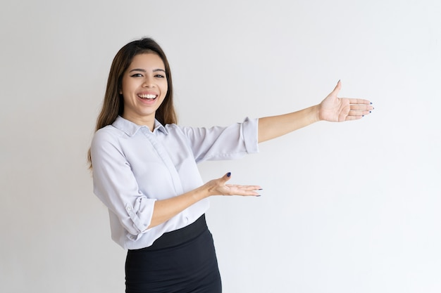 Cheerful beautiful girl presenting new product Free Photo