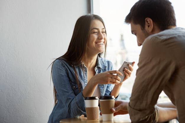 日付のカフェに黒い髪の陽気な美しい女の子が座って、笑って、人生の面白い話を彼氏に話します。幸せの温かい雰囲気。 無料写真