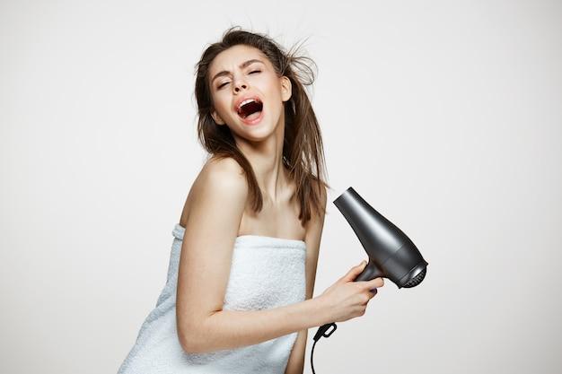 웃 고 얼굴 웃 고 헤어 드라이어로 노래를 웃 고 수건에 쾌활 한 아름 다운 여자. 뷰티 스파 및 미용. 무료 사진
