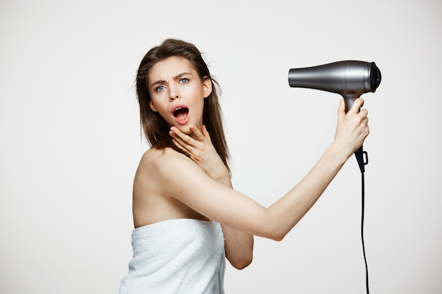 Cheerful beautiful woman in towel smiling laughing singing with hair dryer making funny face. beauty spa and cosmetology. Free Photo