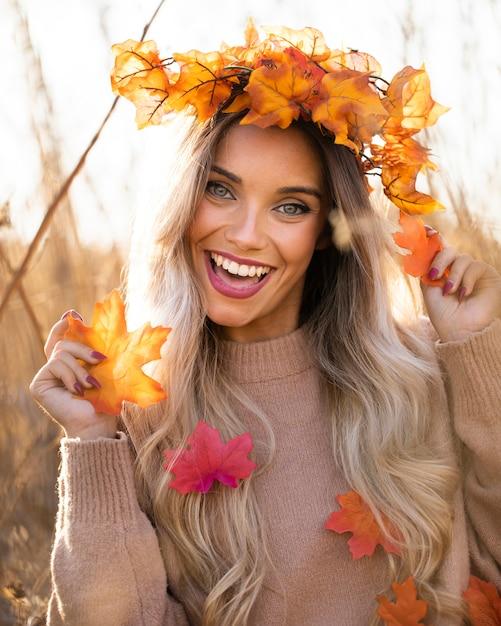 Cheerful beautiful woman wearing maple leaves wreath having fun at outdoors Free Photo