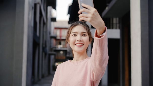 Cheerful beautiful young asian backpacker blogger woman using smartphone taking selfie while traveling at chinatown in beijing, china. Free Photo