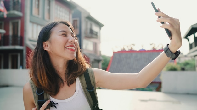 Cheerful beautiful young asian backpacker blogger woman using smartphone taking selfie Free Photo