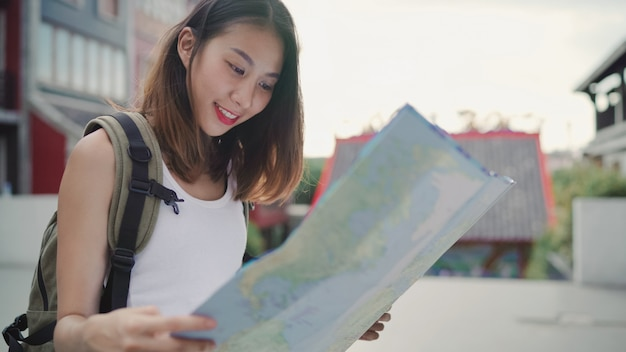 Cheerful beautiful young asian backpacker woman direction and looking on location map Free Photo