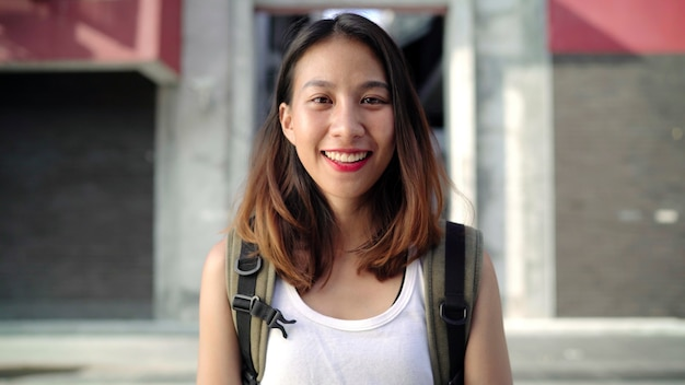 Cheerful beautiful young asian backpacker woman feeling happy smiling to camera Free Photo