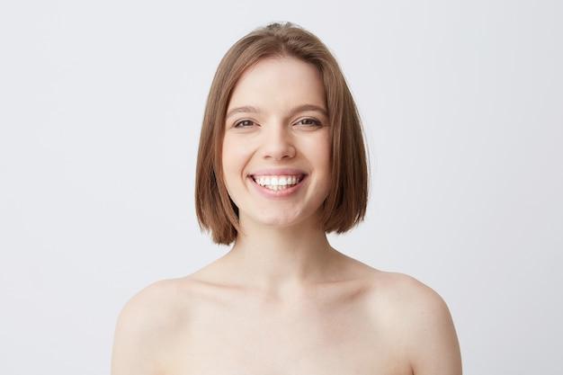 マスクを適用した後、柔らかな肌と健康な歯を持つ黒髪の陽気な美しい若い女性 無料写真