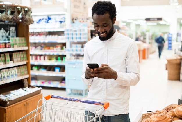 Cheerful black man typing on cellphone in grocery store Free Photo