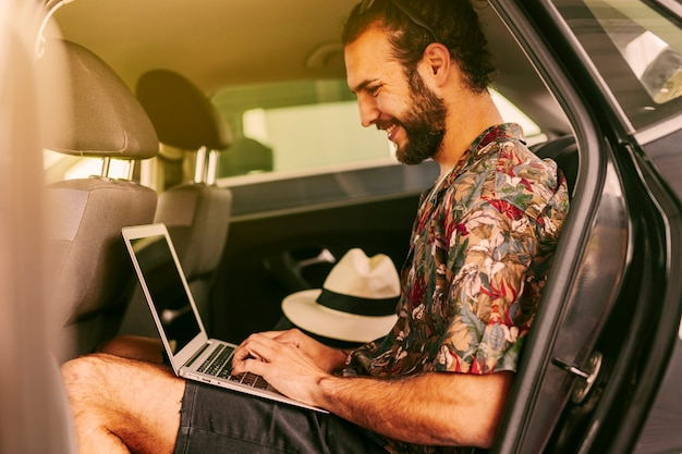 Cheerful blogger using laptop in car Free Photo