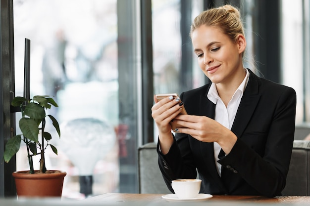 Cheerful blonde business woman using mobile phone Free Photo