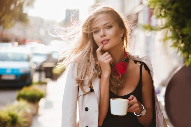 Donna bionda allegra con sorriso ispirato in posa con una tazza di caffè in una giornata di sole. ritratto all'aperto del modello femminile sveglio che tocca il suo labbro con il dito e che tiene il latte in mano. Foto Gratuite