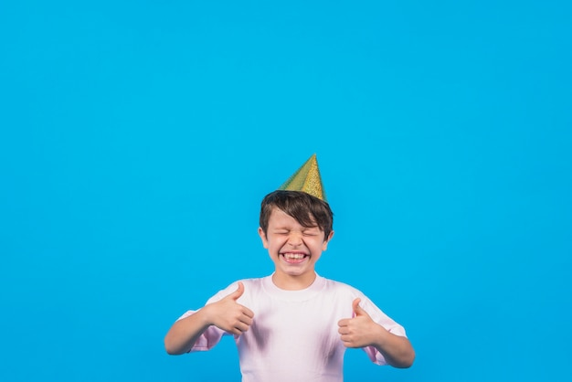 Cheerful boy gesturing thumbup against blur backdrop Free Photo