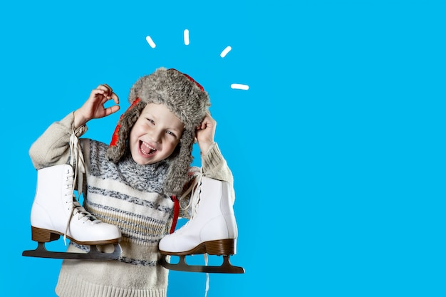 Cheerful boy in a hat with earflaps holding ice skates on blue background Premium Photo