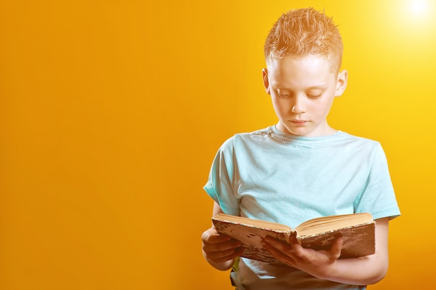 Cheerful boy in a light t-shirt holding a book on a colored Premium Photo