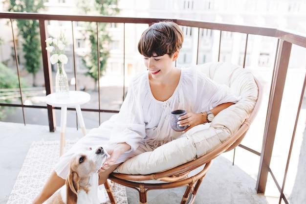 喜んで見上げる面白い子犬をなでるコーヒーのカップを保持している陽気なブルネットの女の子 無料写真