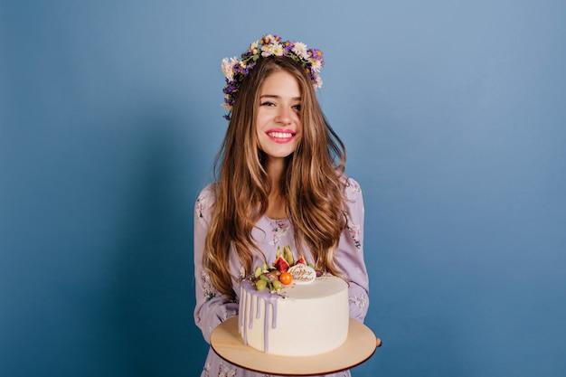 バースデーケーキでポーズをとって花の花輪の陽気なブルネットの女性 無料写真