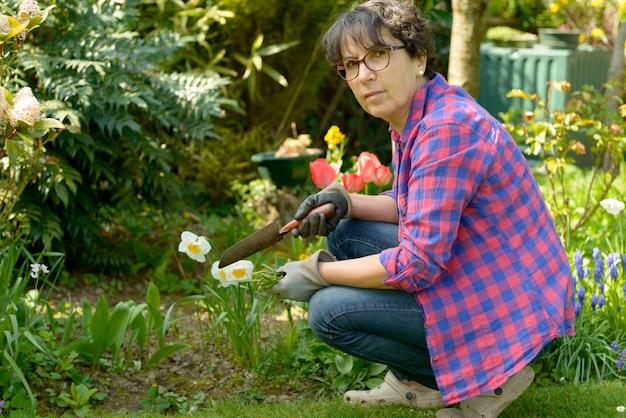 Cheerful brunette woman planting flowers in garden Premium Photo